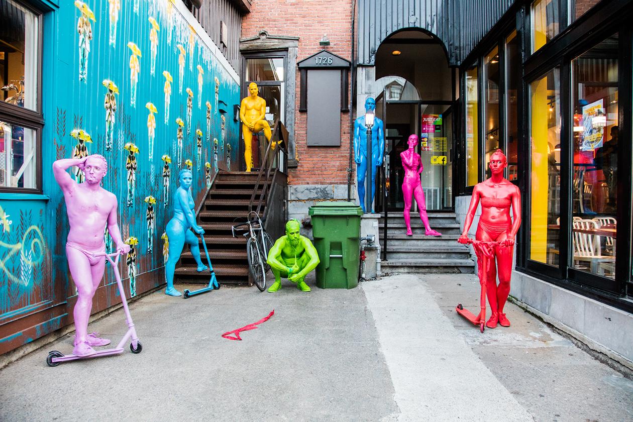 Personnages en trottinette colorés entourés d'art de rue dans une ruelle commerciale pour faire l'animation du parcours piéton