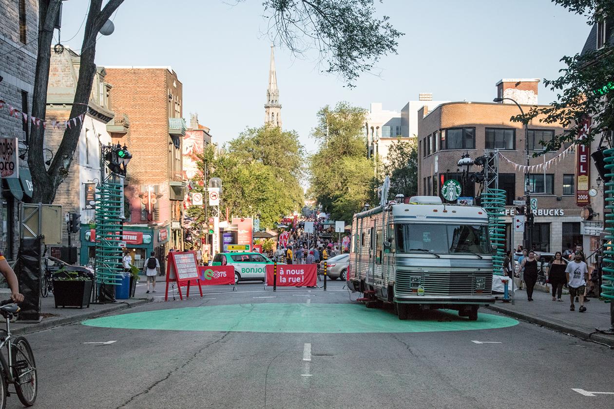Grand cercle peint dans la rue faisant office de scène avec chevalet affichant l'horaire des spectacles et roulotte des artistes