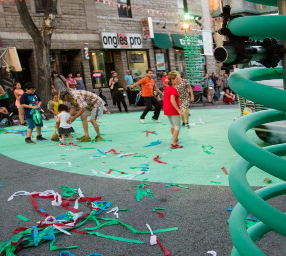 Familles célébrant dans la rue pleine de confettis après une performance de théâtre urbain sur la scène décorée de spring géant