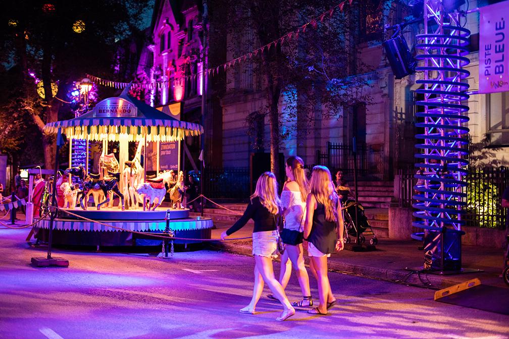 Passantes profitant du nightlife festif marchant vers un carrousel d'amusement devant une façade de monument éclairé en mauve