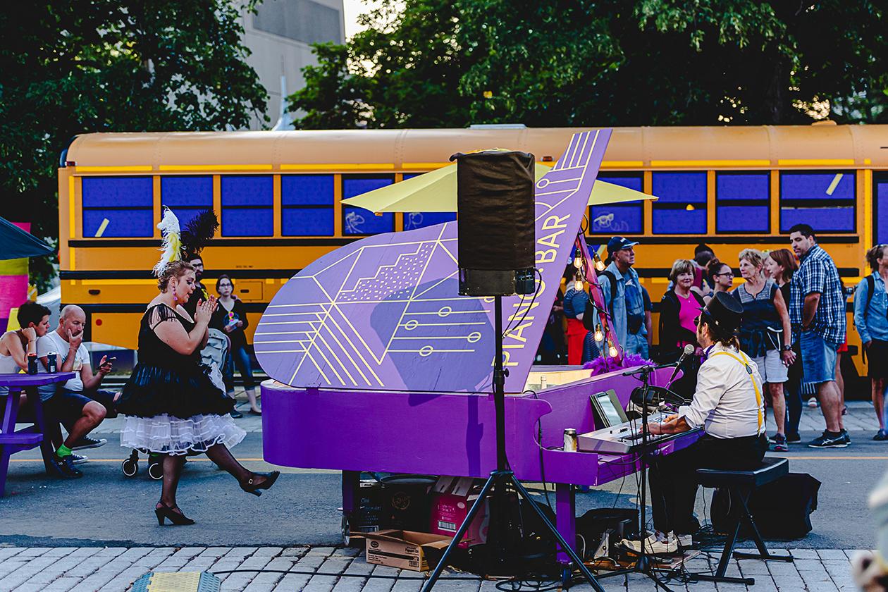 Acteur jouant sur un piano mauve avec motifs géométriques peints en jaune devant un kiosque aménagé dans un autobus scolaire