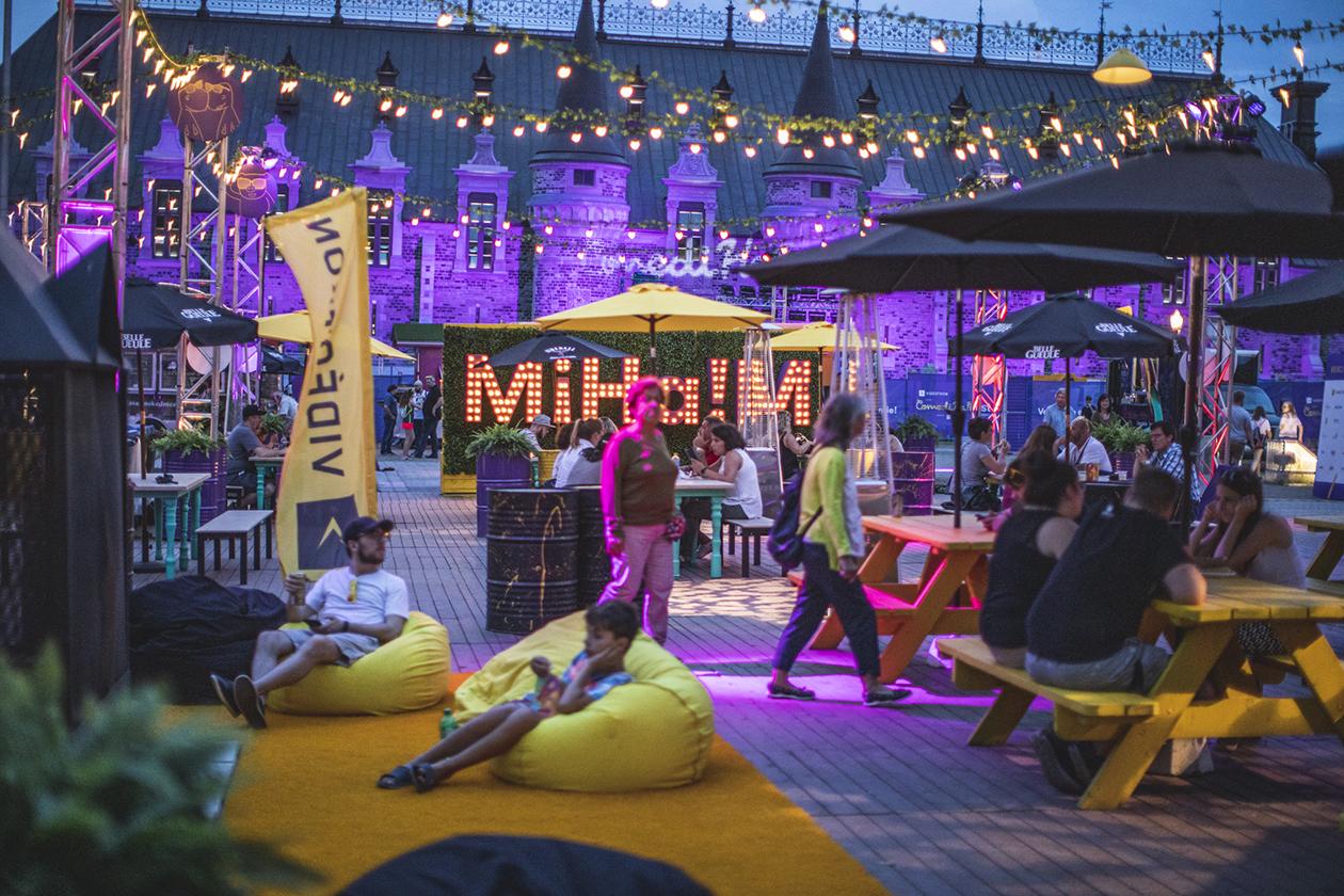 Visiteurs assis sous des parasols aux tables à pique-nique et dans des bean bags sur tapis de sol dans la zone Miha!m le soir