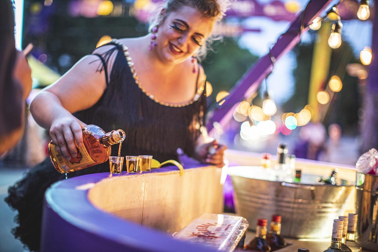 Gros plan d'une animatrice dans son costume versant de l'alcool derrière le bar mauve sur-mesure dans une ambiance festive