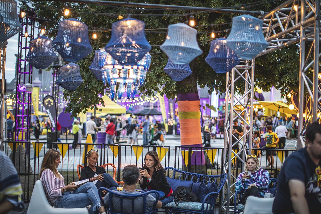 Amis relaxant assis dans le mobilier sur-mesure de la terrasse du bar forain dans le décor funky agrémenté de lampes colorées