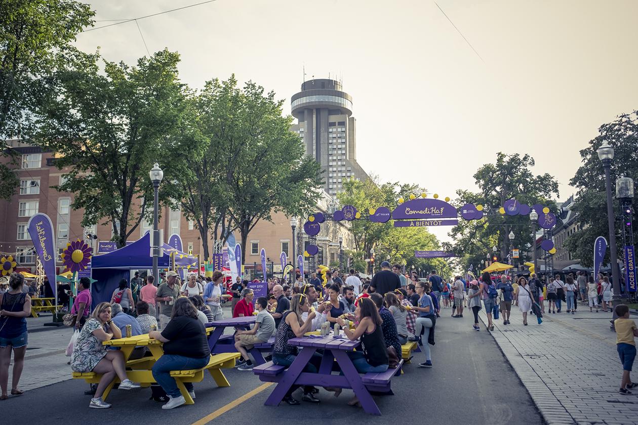 Participants assis pour manger aux tables à pique-nique mauves et jaunes devant l'arche d'entrée du site dans la rue le jour