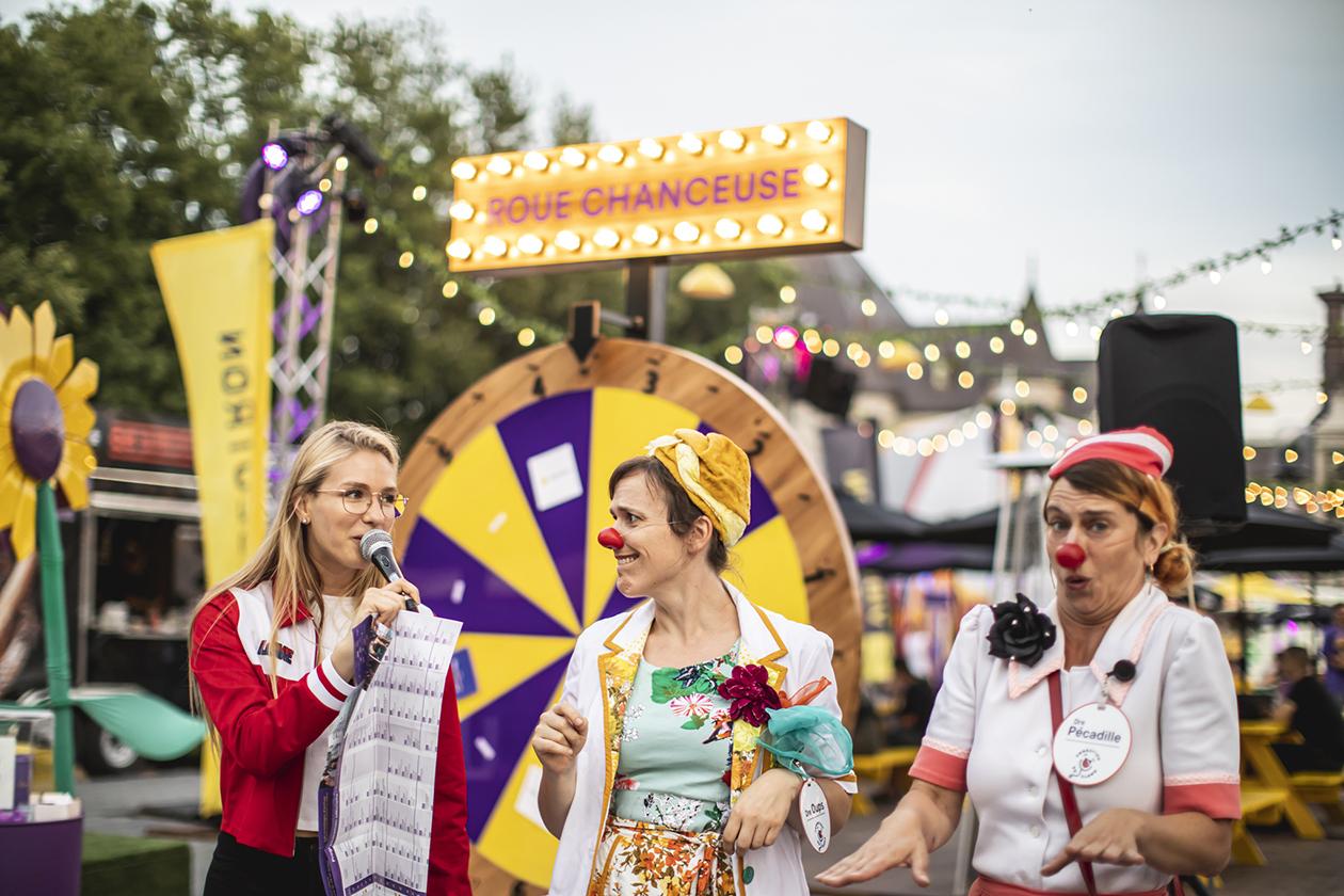 Personnages de cirque costumés devant la roue chanceuse qui tourne pour gagner un prix en plein coeur du décor forain illuminé