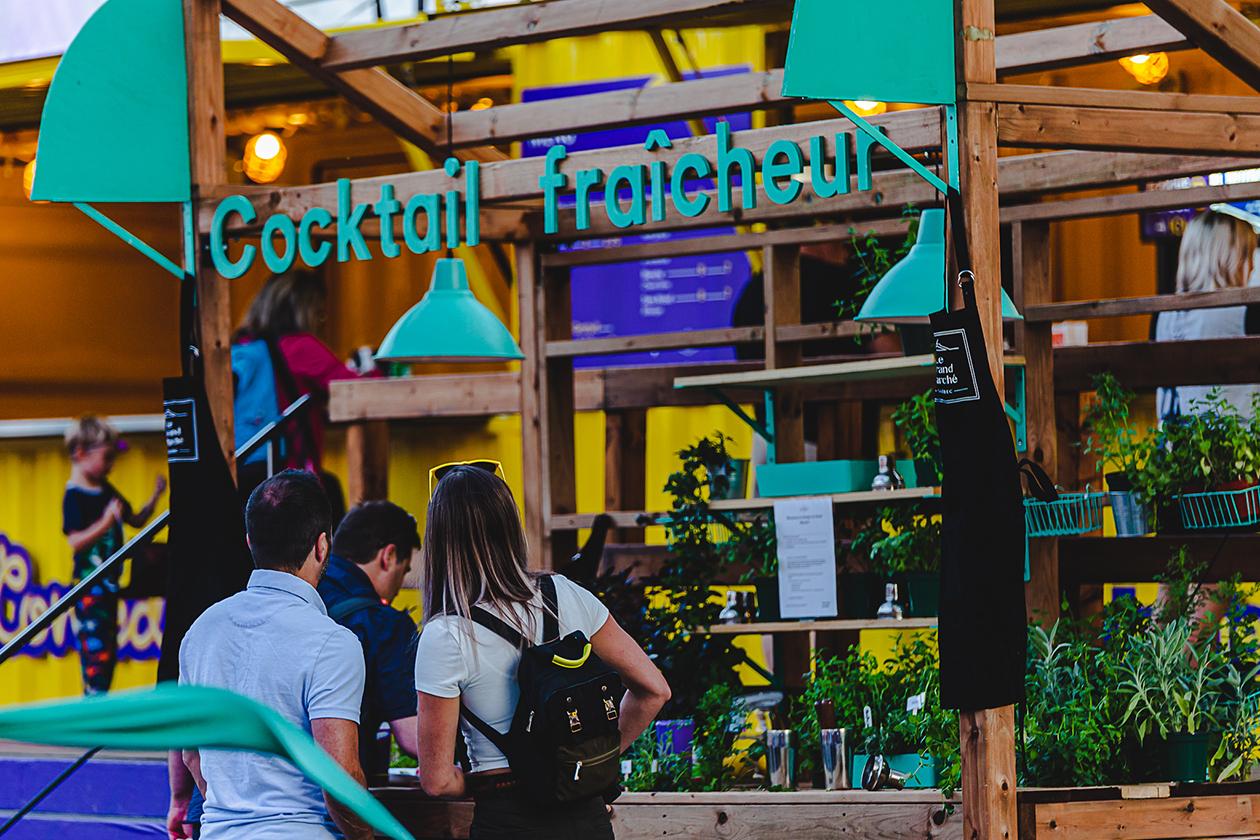 """Participant faisant lui-même son drink au kiosque extérieur """"Cocktail fraîcheur"""" fait de bois et décoré de lampes turquoises"""