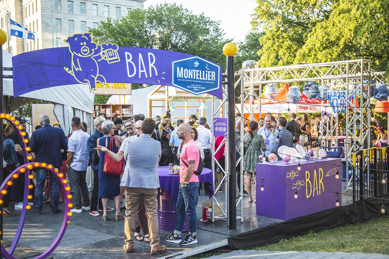 Rassemblement de gens debout autour de barils mauves recyclés profitant du festival dans l'espace bar sous un pont d'éclairage