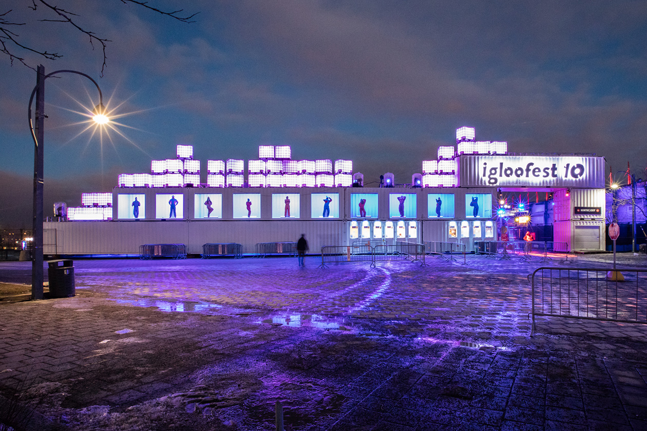 Arche d'entrée éclairée faite de conteneurs empilés avec les silhouettes de dix personnages dans le vieux-port de Montréal