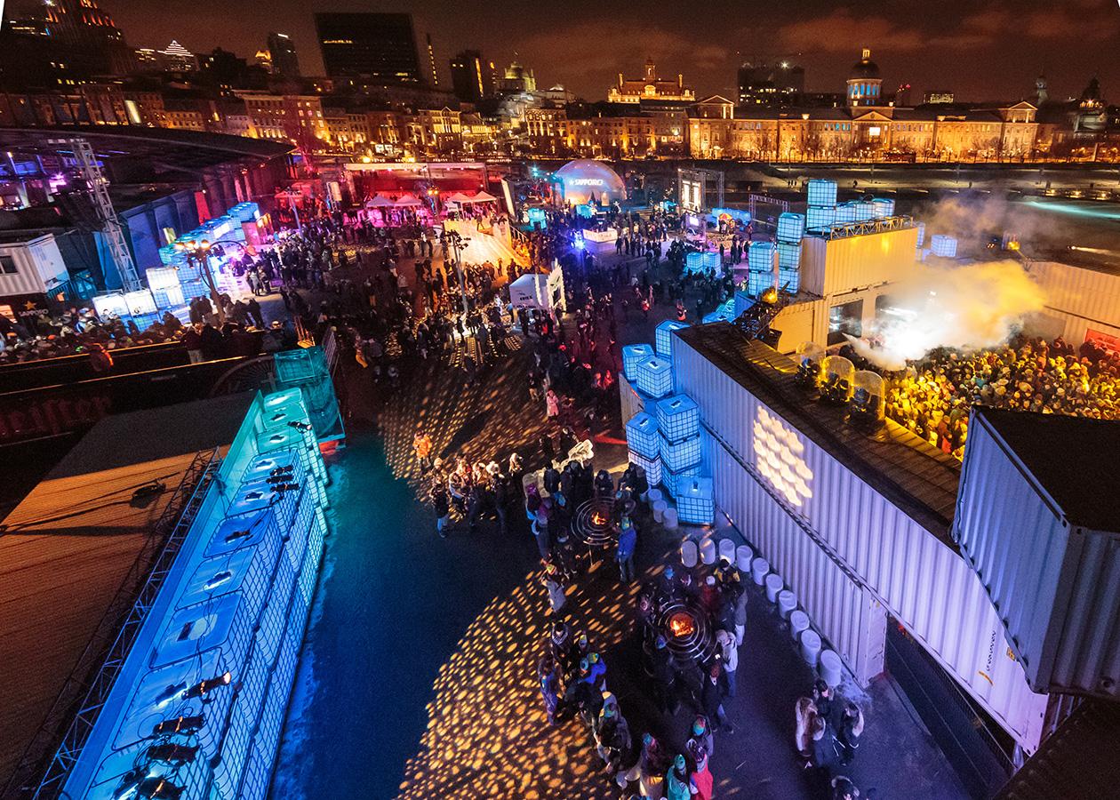 Vue aérienne de l'aménagement montrant la foule dansant près de la scène en containers et des gobos au sol en forme de flocon