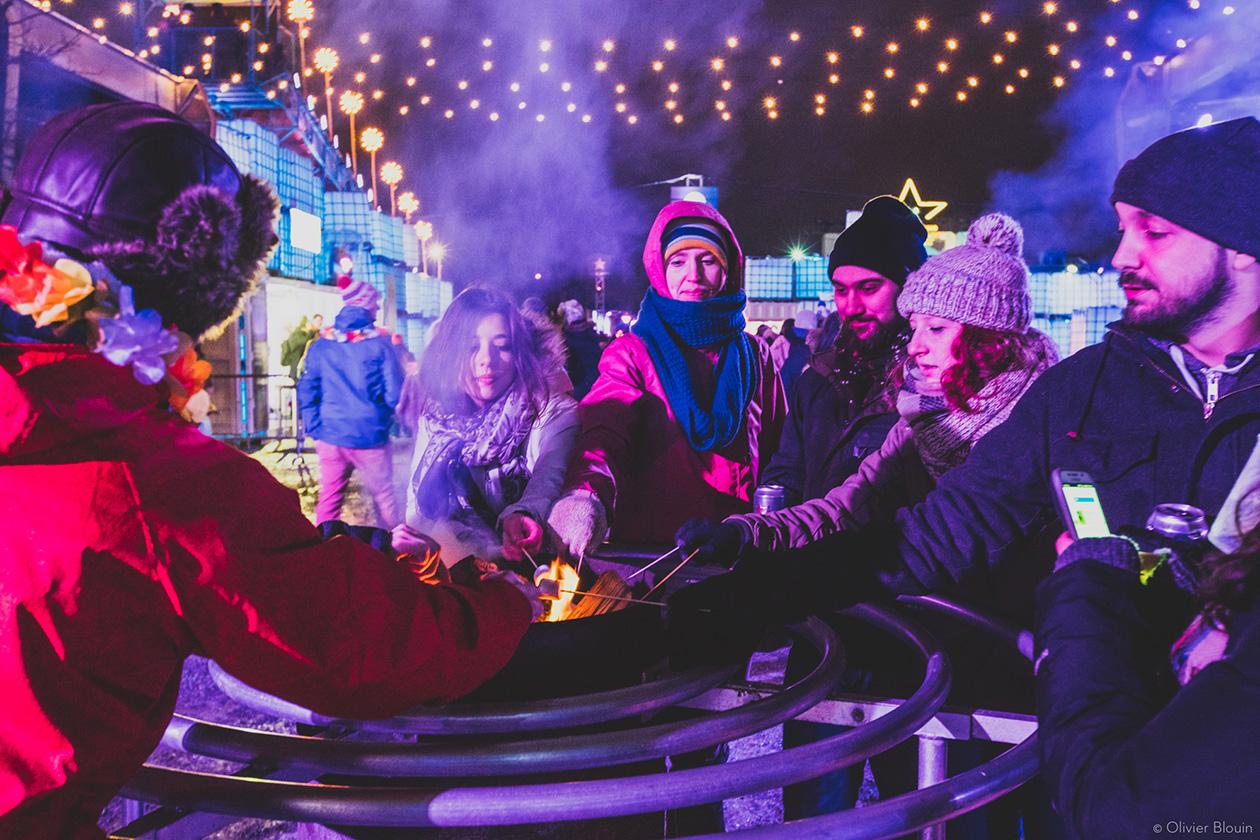 Festivaliers habillés de tuque, mitaines et foulard grillant des guimauves sur un brasero sous l'éclairage des string lights