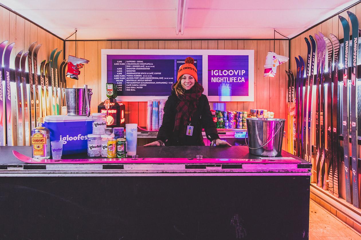 Barmaid derrière le bar à l'intérieur de la roulotte igloofest VIP décorée de vieux skis et de bottes suspendues à l'envers