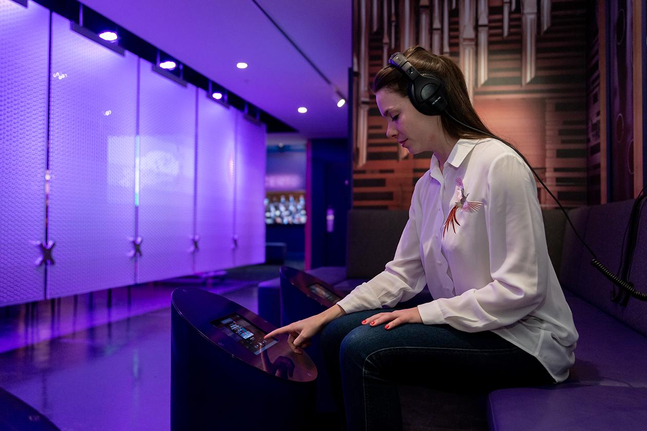Spectatrice avec casque d'écoute effectuant un choix de musique classique sur un menu défilant sur une borne interactive tactile