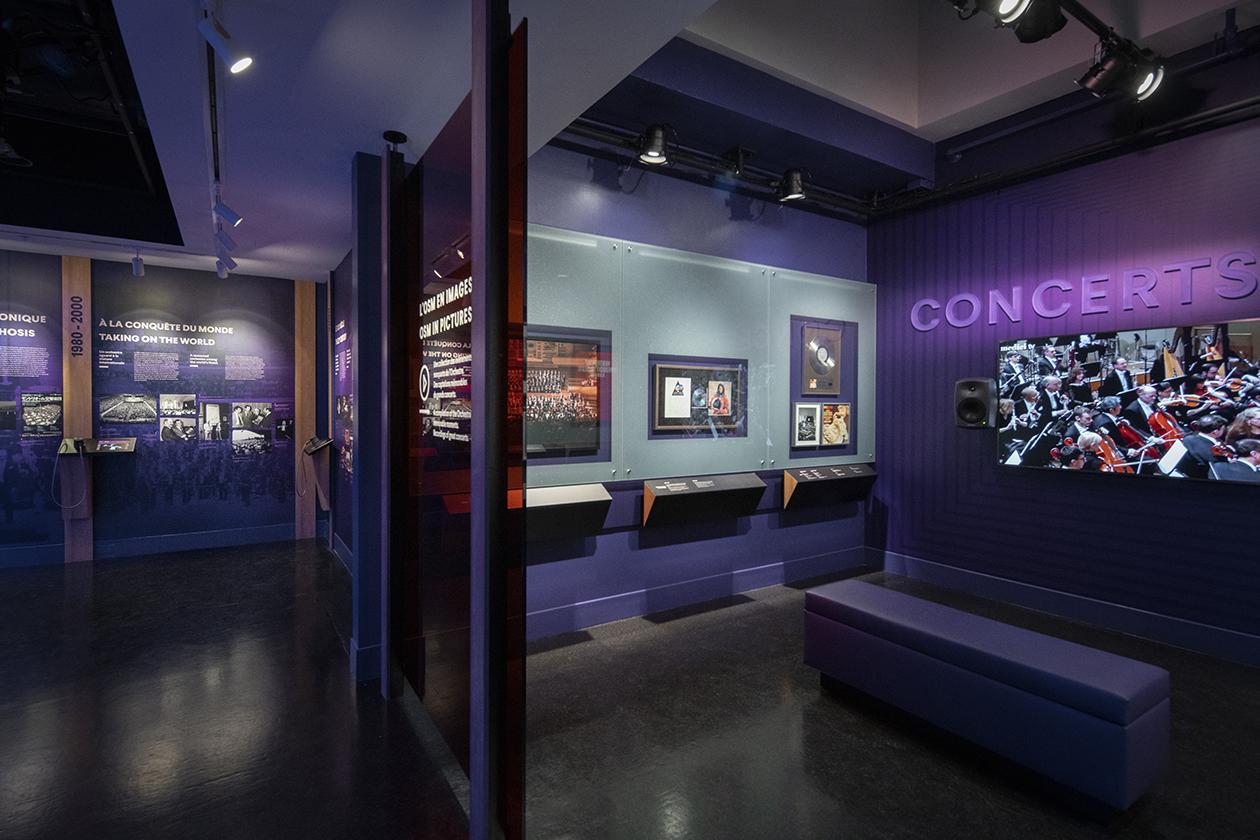 Intérieur de l'atrium avec cadres et télévision au mur diffusant la retransmission sur une télévision de la salle de concert