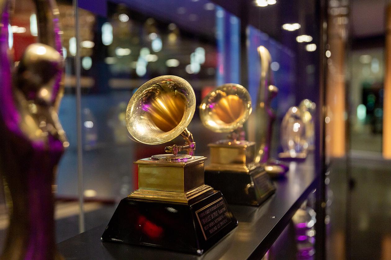 Gros plan des Grammy Awards et autres trophées sur la devanture du mobilier destiné à la présentation des récompenses reçues