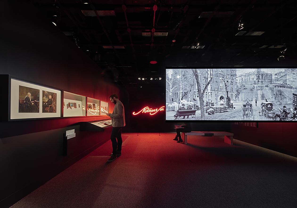Visiteur consultant une fiche informative devant des photographies anciennes dans une galerie contenant un mot en néon allumé