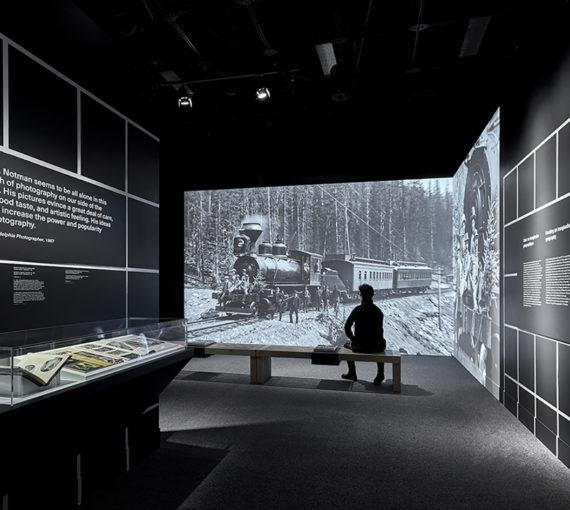 Spectateur assis sur un banc admirant une projection grand format dans une salle contenant un podium et du texte sur les murs