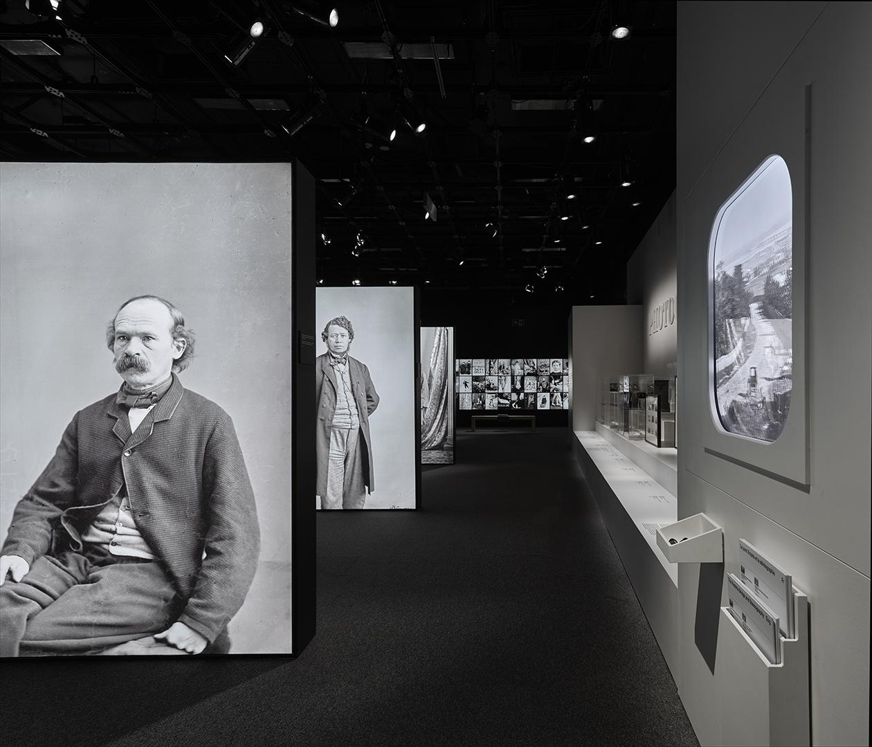 Salle d'expo affichant des boîtes lumineuses de portraits grandeur nature et une mosaïque de clichés de personnages célèbres