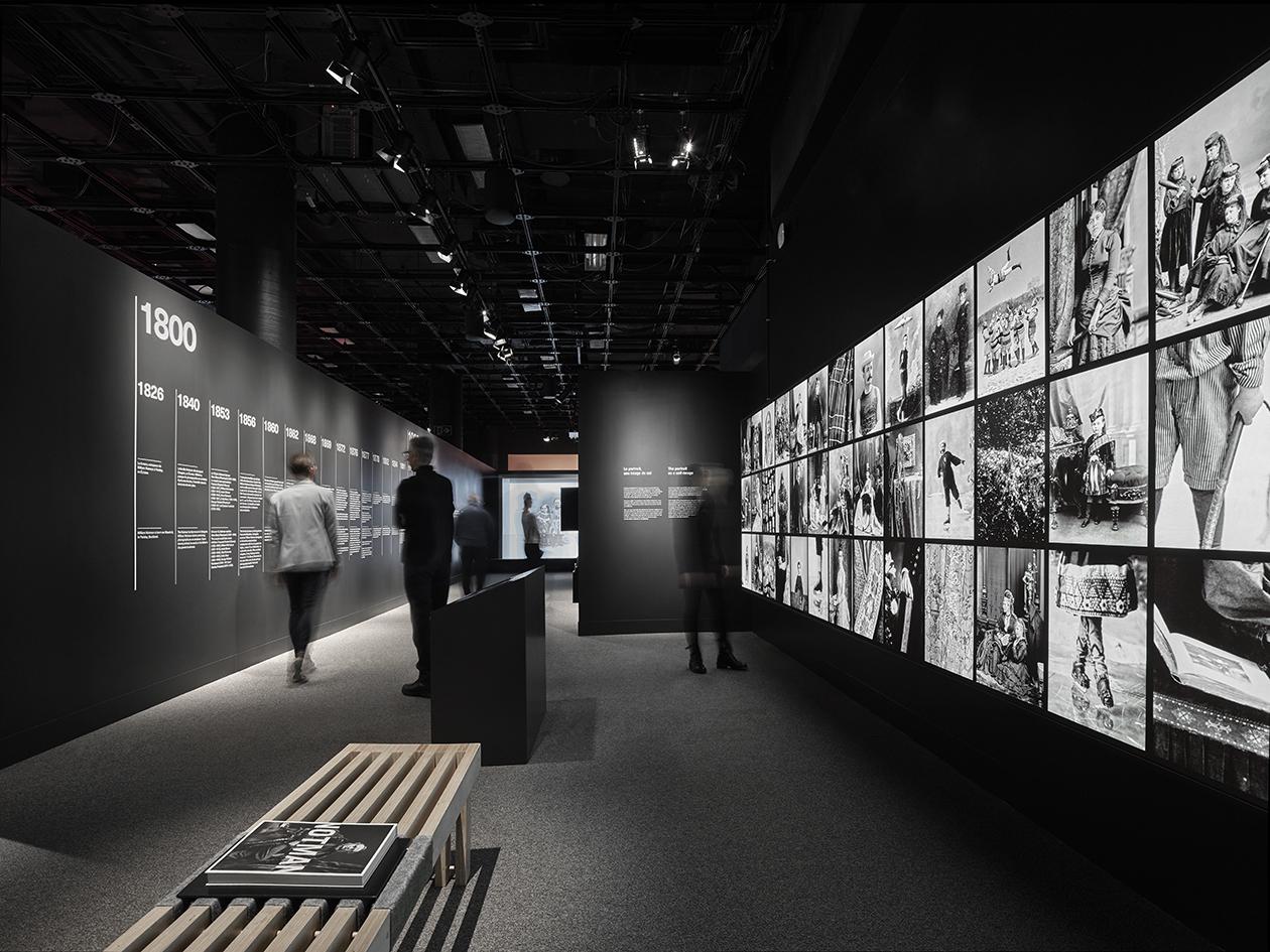 Visiteurs consultant l'explication d'une ligne du temps blanche collée sur un mur noir dans une salle d'exposition informative